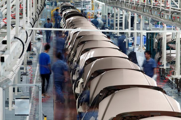 FILE PHOTO: Employees work along a Geely Automobile Corporation assembly line in Cixi, Zhejiang province June 21, 2012. REUTERS/Carlos Barria/File Photo