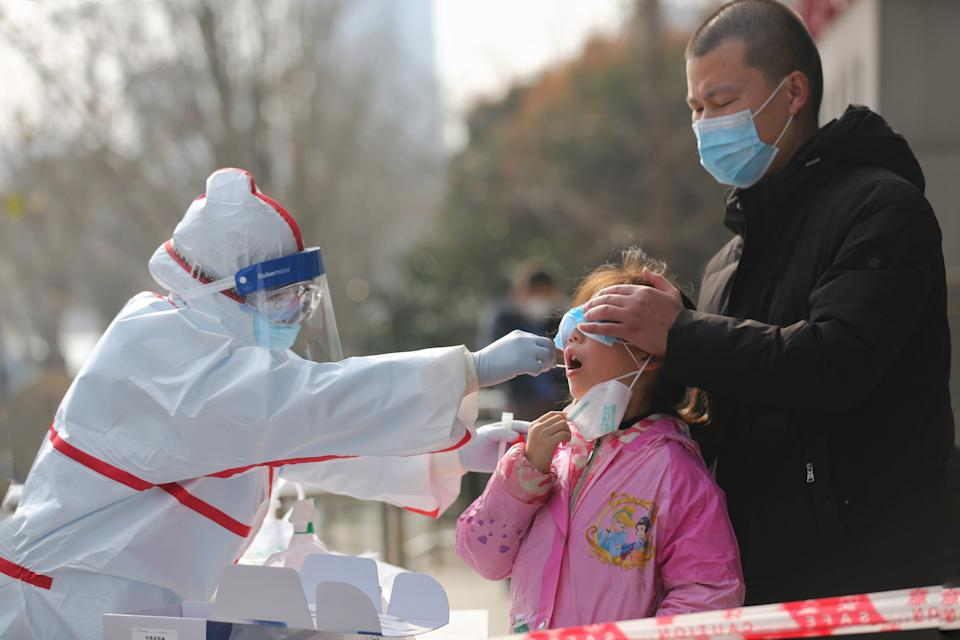 A medical worker takes swab for SARS-COV-2 testing on a resident on the sidewalk in Wuhan in central China's Hubei province Thursday, March 05, 2020. (Photo: Barcroft Media via Getty Images)