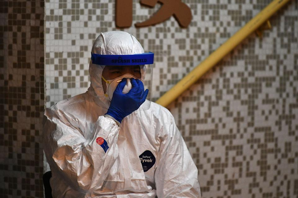 A medical personnel wearing a protective suit checks his mask as he waits near a block's entrance in the ground of a residential estate, in Hong Kong, early on February 11, 2020, after two people in the block were confirmed to have contracted the coronavirus according to local newspaper reports. (Photo by Anthony WALLACE / AFP) (Photo by ANTHONY WALLACE/AFP via Getty Images)