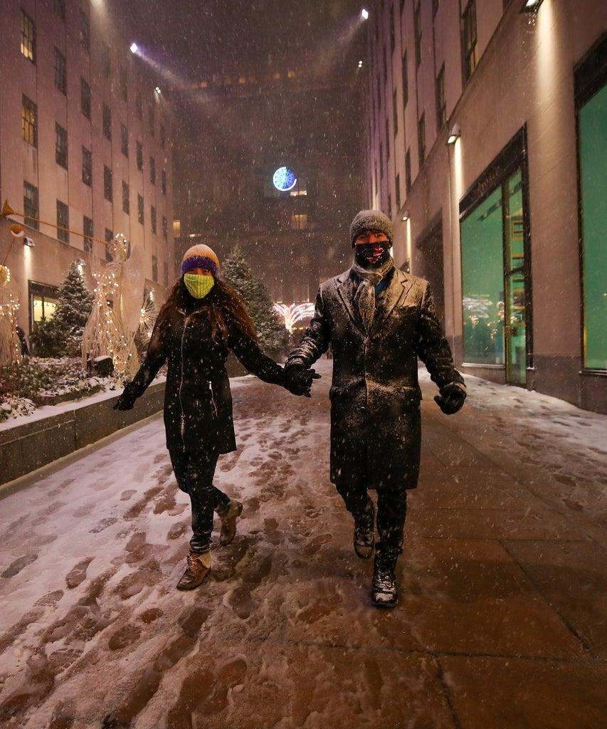 NEW YORK, USA – DECEMBER 16: A couple is seen at the Rockefeller Center during snowfall in New York City, United States on December 16, 2020. (Photo by Tayfun Coskun/Anadolu Agency via Getty Images)