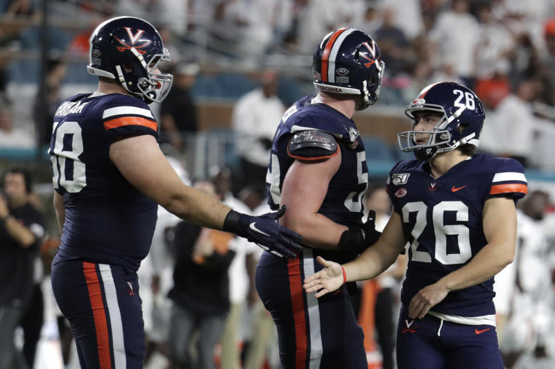 Virginia place kicker Brian Delaney (26) is congratulated by defensive tackle Eli Hanback (58) after making field goal during the first half of an NCAA college football game against Miami, Friday, Oct. 11, 2019, in Miami Gardens, Fla. (AP Photo/Lynne Sladky)