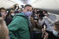 FILE - In this Jan. 17, 2021, file photo, Alexei Navalny is surrounded by journalists in a plane before a flight to Moscow in the Berlin Brandenburg Airport. A prison sentence for Russian opposition leader Alexei Navalny and a sweeping crackdown on protesters demanding his release reflect the Kremlin's steely determination to fend off threats to its political monopoly at any cost. (AP Photo/Mstyslav Chernov, File)