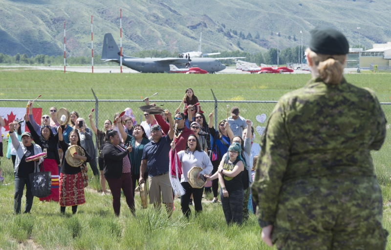 First Nations drummers salute Royal Canadian Air Force Public Affairs Officer Lt. Alexandra Hejduk during a drum ceremony to remember fallen Snowbirds Capt. Jenn Casey in Kamloops, B.C., Monday, May 18, 2020. Capt.Casey died Sunday after the Snowbirds jet she was in crashed shortly after takeoff. The pilot of the aircraft is in hospital with serious injuries. (Jonathan Hayward/The Canadian Press via AP)