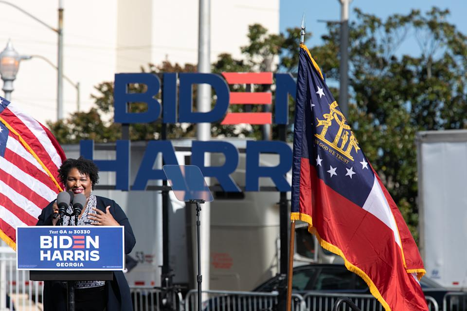 Stacey Abrams speaks at a podium at a Biden/Harris rally