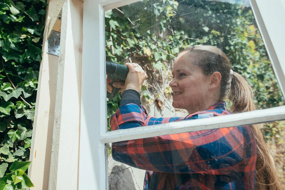 Smiling woman building up greenhouse at home.