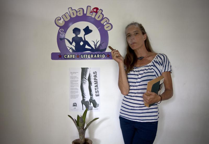 """U.S. citizen Conner Gorry smokes a cigar as she poses for a portrait next to the logo of a new English-language bookstore, cafe and literary salon """"Cuba Libro,"""" a group-owned private enterprise she is part of with five Cubans in Havana, Cuba, Friday, Aug. 9, 2013. """"I know how hard it is to get English-language sources here,"""" said New York City native Gorry, 43, a journalist living in Cuba since 2002. """"So I started cooking this idea."""" (AP Photo/Ramon Espinosa)"""