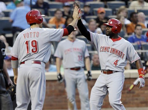 Cincinnati Reds' Brandon Phillips (4) celebrates with teammate Joey Votto (19) after hitting a two-run home run during the third inning of a baseball game against the New York Mets on Friday, June 15, 2012, in New York. (AP Photo/Frank Franklin II)