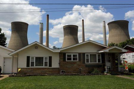 File photo of the John Amos coal-fired power plant behind a home in Poca West Virginia