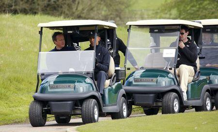 U.S. President Barack Obama and British Prime Minister David Cameron ride in a cart together during a round of golf at The Grove golf course in Watford, England, April 23, 2016.REUTERS/Kevin Lamarque