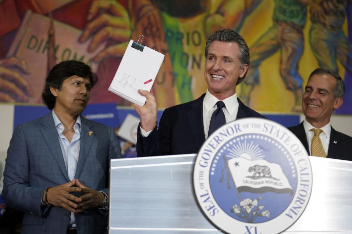 California Gov. Gavin Newsom, center, holds up the California Comeback Plan relief bill after signing it next to Los Angeles City councilman Kevin de Leon, left, and Los Angeles Mayor Eric Garcetti Tuesday, July 13, 2021, in Los Angeles. (AP Photo/Marcio Jose Sanchez)