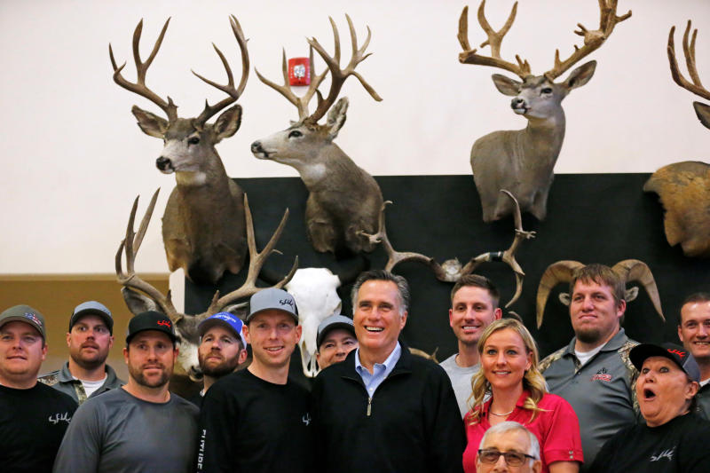 In this Friday, March 2, 2018 photo, Mitt Romney poses with a group at the Sportsmen for Fish and Wildlife Banquet during a campaign stop, in Blanding, Utah. Romney is gearing up for arguably the biggest challenge of his Senate campaign: A Utah Republican party convention where he'll have to face down nearly a dozen contenders in front of a far-right-leaning audience. (AP Photo/Rick Bowmer, File)