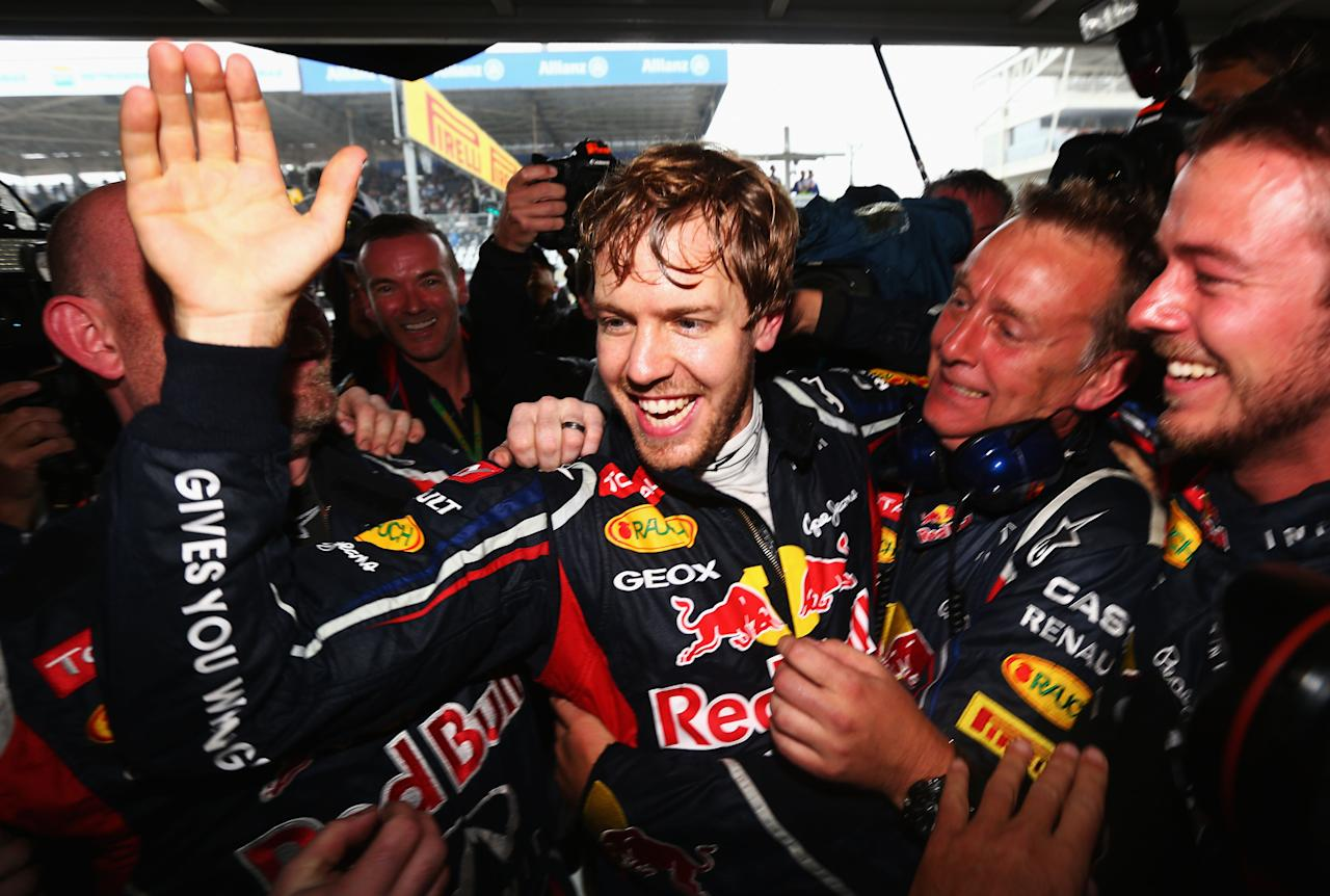 SAO PAULO, BRAZIL - NOVEMBER 25:  Sebastian Vettel of Germany and Red Bull Racing celebrates with team mates in his garage as he clinches the drivers world championship during the Brazilian Formula One Grand Prix at the Autodromo Jose Carlos Pace on November 25, 2012 in Sao Paulo, Brazil.  (Photo by Paul Gilham/Getty Images)
