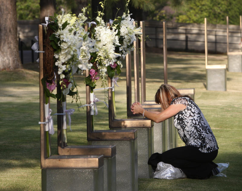 Regina Bonny, a retired Midwest City, Okla., police officer from Moore, Okla., kneels at the chair of DEA agent Kenneth Glenn McCullough in the field of chairs at the Oklahoma City National Memorial and Museum in Oklahoma City, Tuesday, April 19, 2011, on the 16th anniversary of the Oklahoma City bombing. (AP Photo/Sue Ogrocki)
