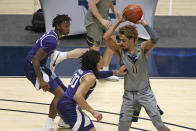West Virginia forward Emmitt Matthews Jr. (11) is defended by Kansas State guards DaJuan Gordon (3) and Mike McGuirl (0)] during the first half of an NCAA college basketball game Saturday, Feb. 27, 2021, in Morgantown, W.Va. (AP Photo/Kathleen Batten)
