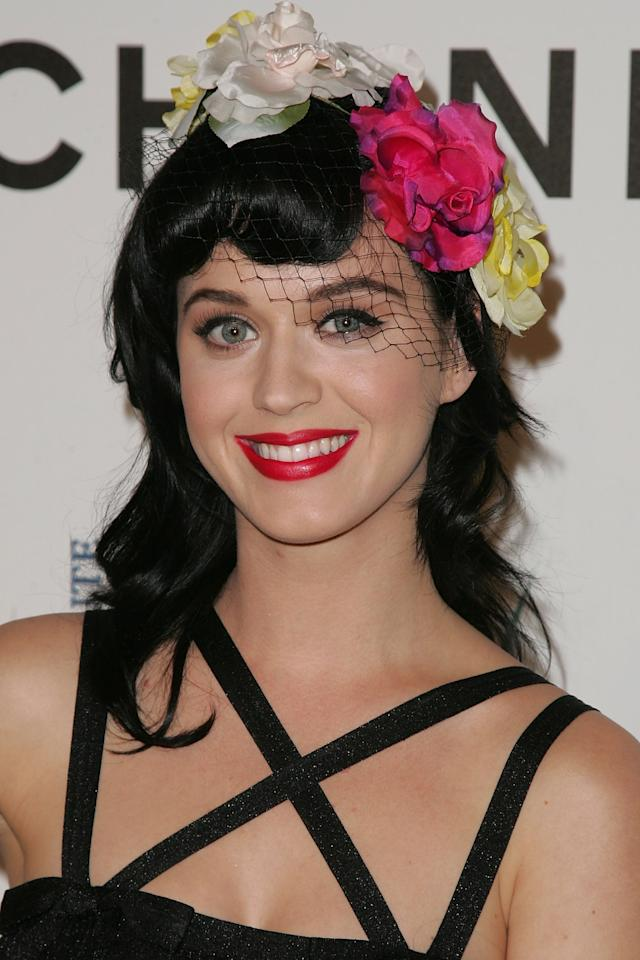 """<p>Perry was a standout at a 2008 event for Chanel with her pop of hot pink lipstick, perfectly coordinated with the pink flower in <a href=""""https://www.popsugar.com/fashion/How-Wear-Headbands-46048718"""" class=""""ga-track"""" data-ga-category=""""Related"""" data-ga-label=""""http://www.popsugar.com/fashion/How-Wear-Headbands-46048718"""" data-ga-action=""""In-Line Links"""">her headband</a>. </p>"""