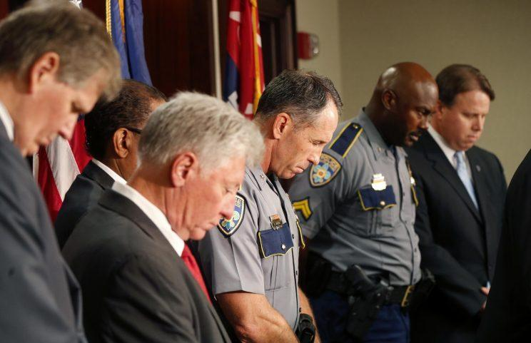 Baton Rouge police chief Carl Dabadie, Jr. center, bows his head in prayer with other officials at the start of a news conference at police headquarters in Baton Rouge, La., Wednesday, July 6, 2016. (Photo: Gerald Herbert/AP)