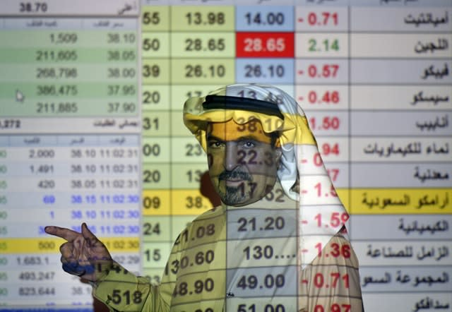 A trader talks to others in front of a screen displaying Saudi stock market values at the Arab National Bank in Riyadh, Saudi Arabia