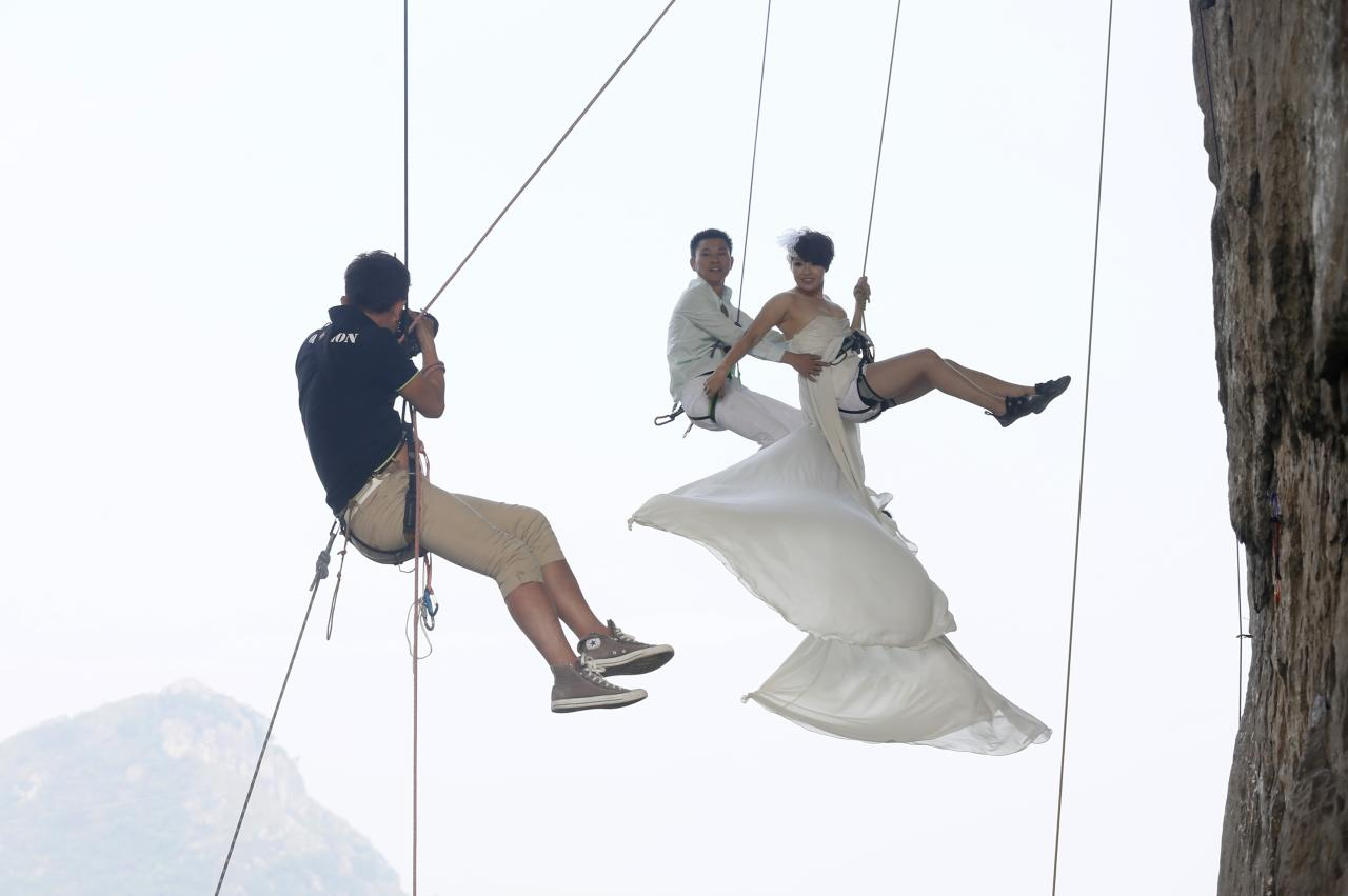 A photographer takes pictures of Fang Jing (R) in a wedding gown next to her husband, surnamed Zhao, as they hang from a cliff during a rock climbing exercise in Liuzhou, Guangxi Zhuang Autonomous Region October 26, 2013. The couple love outdoor sports and they decided to have their wedding photos taken during rock climbing, local media reported. Picture taken October 26, 2013. REUTERS/Stringer (CHINA - Tags: SOCIETY SPORT TPX IMAGES OF THE DAY) CHINA OUT. NO COMMERCIAL OR EDITORIAL SALES IN CHINA