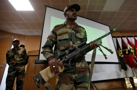 An Indian Army soldier displays a seized rifle during a news conference in Srinagar