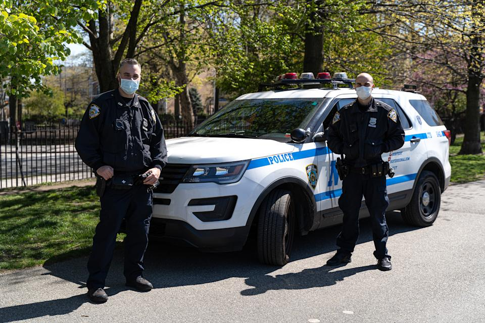 NEW YORK, NEW YORK - APRIL 28:  NYPD police officers while wearing protective face masks pose in front of Police SUV in McCarren park on April 28, 2020 in Williamsburg, Brooklyn, New York (Photo by Jared Siskin/Getty Images)