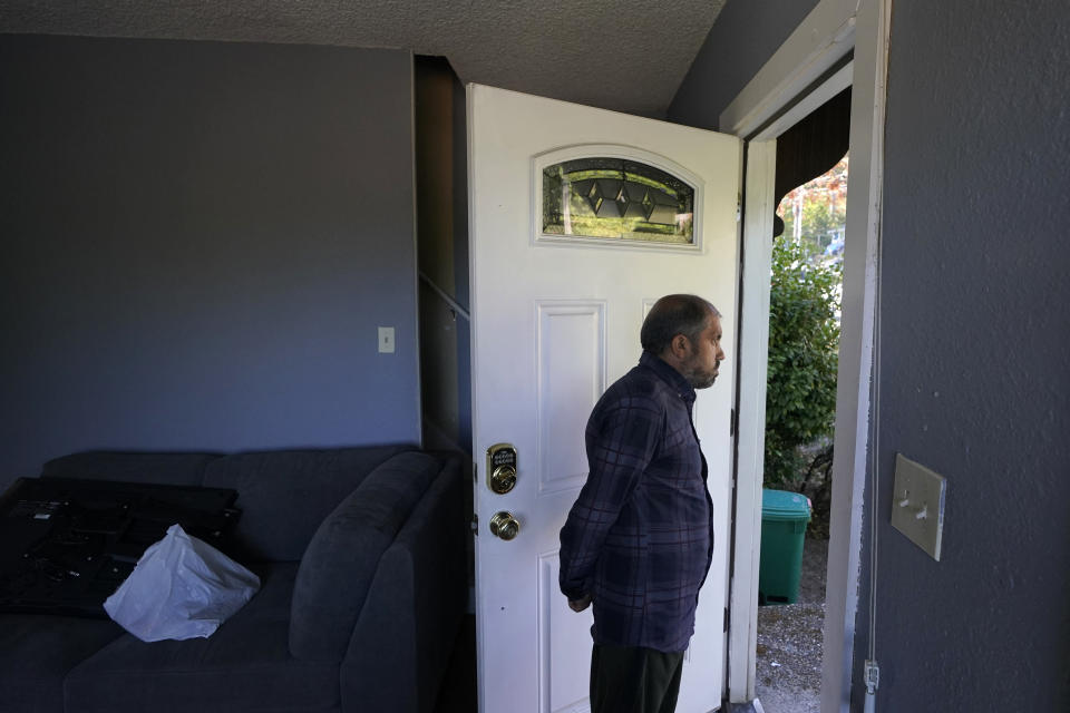 Abdul, who worked as a mechanic before he left Kabul, Afghanistan with his family about a month ago, looks out the doorway of a rental house, Thursday, Sept. 16, 2021, where his family have been provided a place to stay in Seattle. The home is owned by Thuy Do, who was nine years old when her family arrived in the United States from Vietnam in the 1980s. Now Do and her husband have offered their vacant rental home to refugee resettlement groups to house newly arriving Afghans in need of a place to stay. (AP Photo/Ted S. Warren)