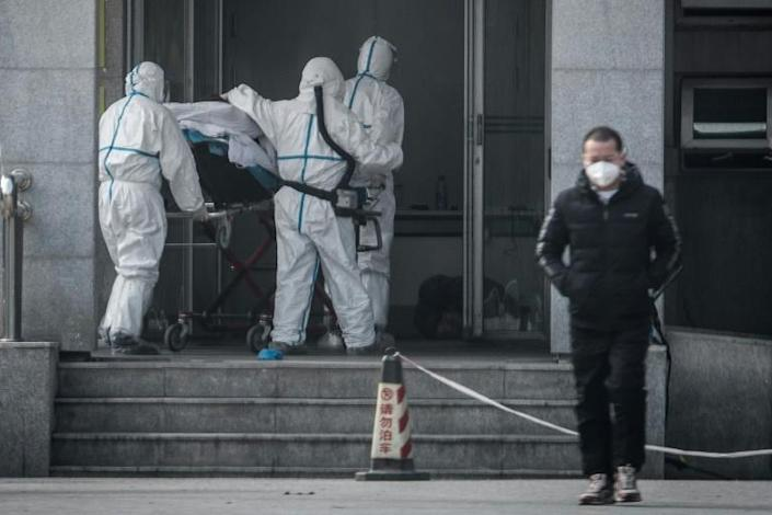 Medical workers carry a patient into a hospital for patients infected with the new coronavirus strain in Wuhan, China (AFP Photo/STR)