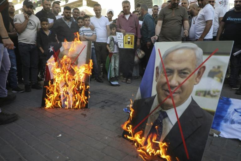 Palestinian demonstrators burn pictures of US President Donald Trump and Israeli Prime Minister Benjamin Netanyahu during a demonstration against the plans to annex parts of the occupied West Bank on May 30