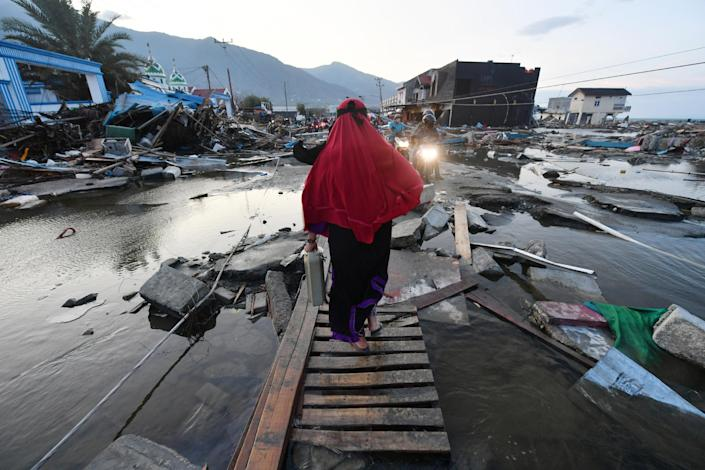 <p>A woman walks through a devastated area in Palu, Indonesia's Central Sulawesi on Oct. 1, 2018, after an earthquake and tsunami hit the area on Sept. 28. (Photo: Adek Berry/AFP/Getty Images) </p>