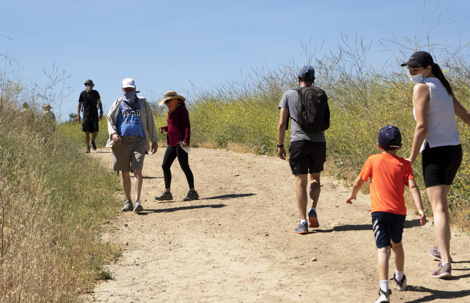 Visitors wear protective masks and social distance on a walk along a popular hiking trail along the Santa Monica mountain range in the Encino section of Los Angeles on May 16, 2020. (AP Photo/Richard Vogel)