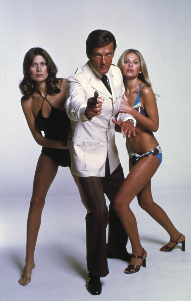 "This undated publicity photo provided by United Artists and Danjaq, LLC shows Roger Moore, center, with Maud Adams, left, and Britt Ekland, from the James Bond 1974 film, ""The Man with the Golden Gun."" Whatever their role, Bond girls still must be inarguably beautiful.The film is included in the MGM and 20th Century Fox Home Entertainment Blu-Ray ""Bond 50"" anniversary set. (AP Photo/United Artists and Danjaq, LLC)"