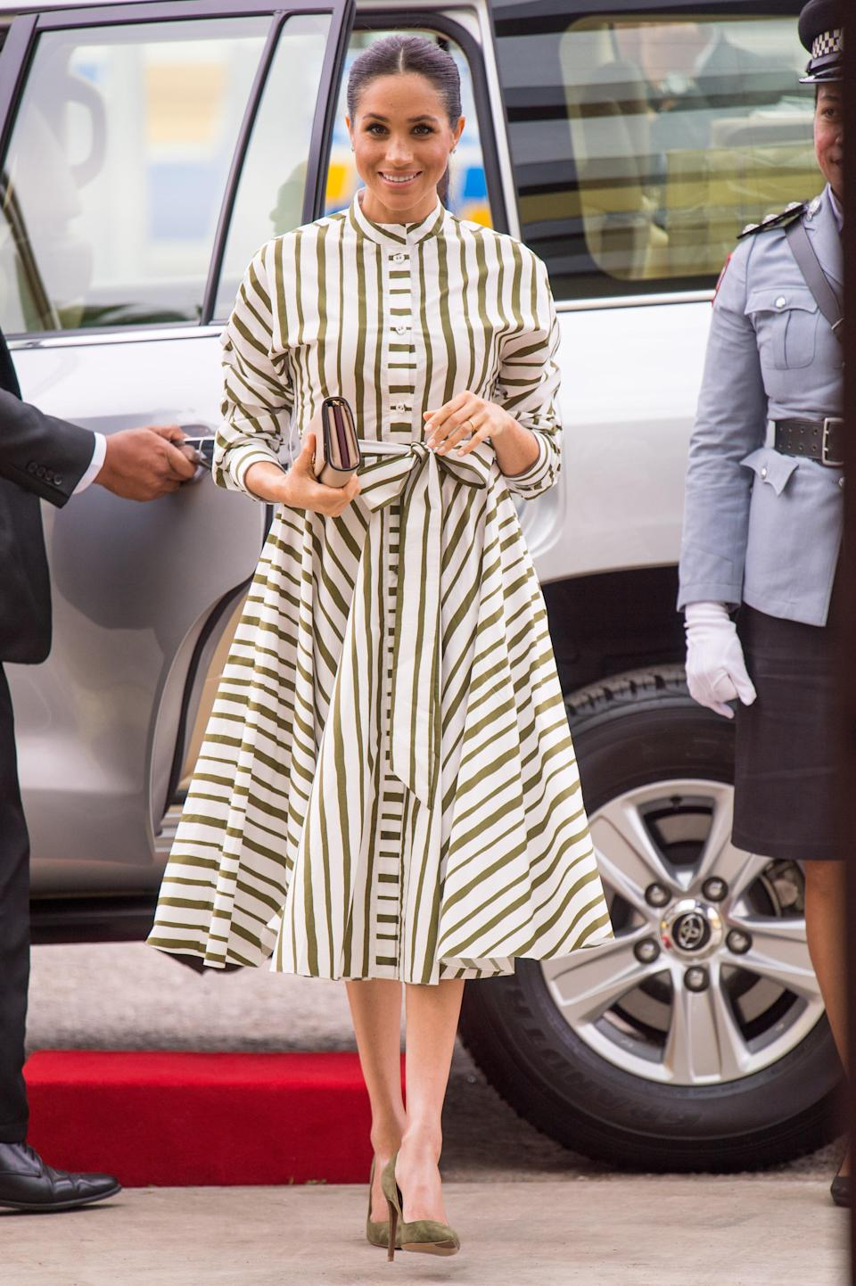 <p>On October 26, Meghan dressed in a striped midi dress by Martin Grant – a label she looked to throughout the tour. She accessorised the look with a Prada clutch, stud earrings from Birks and olive green shoes. <em>[Photo: Getty]</em> </p>