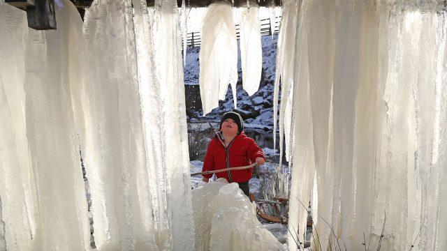 Three-year-old Reuben looks at a wall of icicles formed in County Durham (Owen Humphreys/PA)
