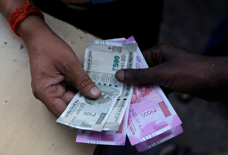 FILE PHOTO: A customer hands Indian currency notes to an attendant at a fuel station in Mumbai