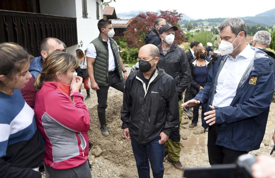 FILE - In this July 18, 2021 file photo Markus Soeder, right, chairman of the CSU and Bavarian minister-president, and Olaf Scholz, center, federal finance minister and candidate for chancellor, talk with residents affected by flooding in Schoenau, Germany. (Felix Hoerhager/dpa via AP)