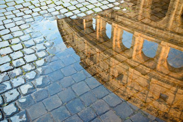 Coliseum reflected in a puddle and cobblestones. Roma Italy