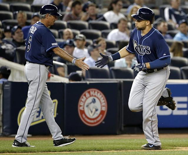 Tampa Bay Rays third base coach Tom Foley, left, congratulates the Rays' James Loney after Loney hit a sixth-inning, solo home run in a baseball game against the New York Yankees at Yankee Stadium in New York, Tuesday, July 1, 2014. (AP Photo/Kathy Willens)