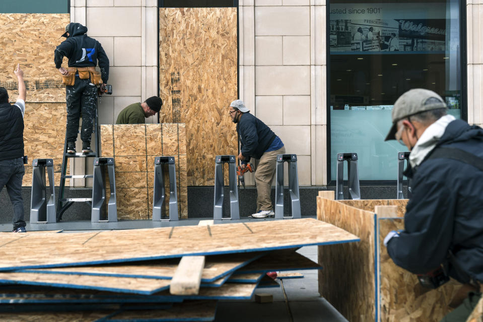 Workers with Baguer Construction LLC board up a Walgreens on U Street NW, Friday, Oct. 30, 2020, in Washington. The site manager said they had been hired to put protective coverings on several Walgreens throughout the city ahead of the election. (AP Photo/Jacquelyn Martin)