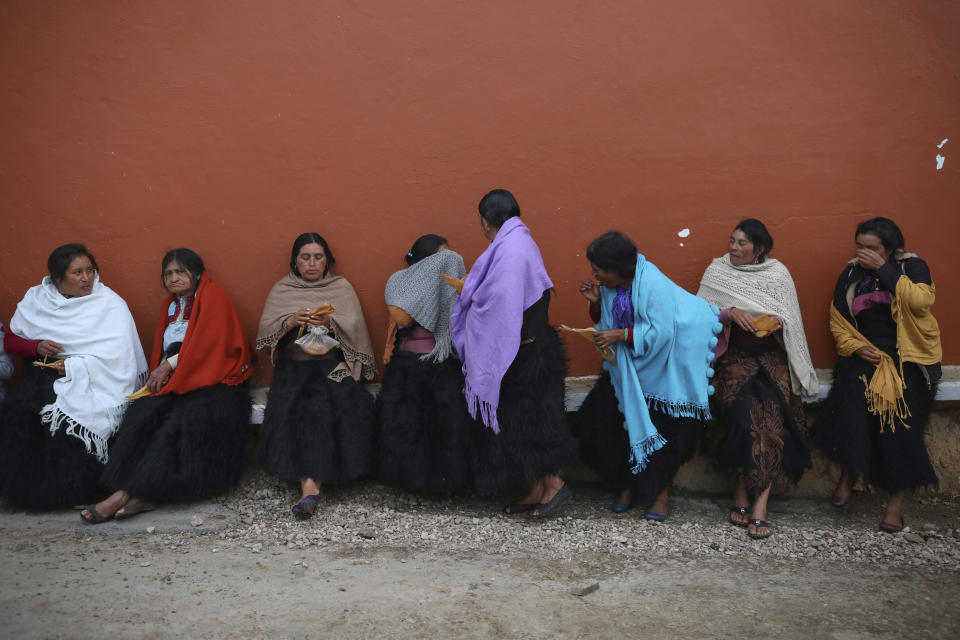 Indigenous Tzotzil women eat breakfast during a non-binding national referendum on whether Mexican ex-presidents should be tried for any illegal acts during their time in office, in the Corazon de Maria community of Chiapas state, Mexico, Sunday, Aug. 1, 2021. (AP Photo/Emilio Espejel)