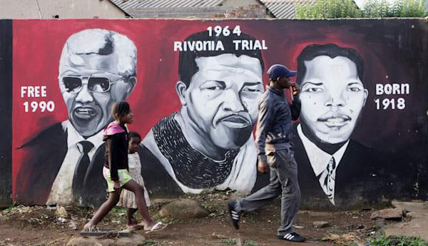 Children passing a Nelson Mandela wall mural in the Township Soweto, Johannesburg, South Africa