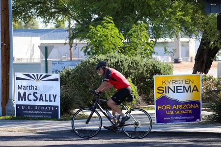 FILE PHOTO: A man rides a bicycle past campaign signs for Arizona U.S. senatorial candidates Krysten Sinema and Martha McSally following the U.S. Midterm elections in Scottsdale, Arizona, U.S. November 7, 2018.   REUTERS/Elijah Nouvelage/File Photo