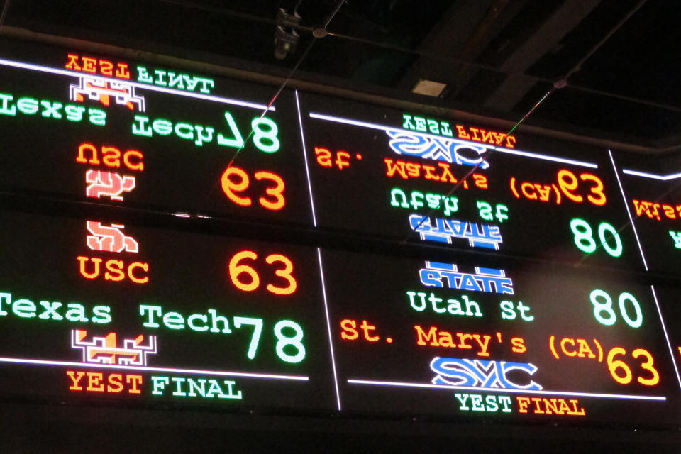 In this Nov. 20, 2018 photo a scrolling video board with basketball scores is reflected in the ceiling of a sportsbook in Atlantic City, N.J. On Thursday, March 11, 2021, BetMGM and Buffalo Wild Wings launched a program where special sports betting products are offered to customers at one of the chain's restaurants in New Jersey, Colorado, Indiana, Iowa, Tennessee and West Virginia. (AP Photo/Wayne Parry)