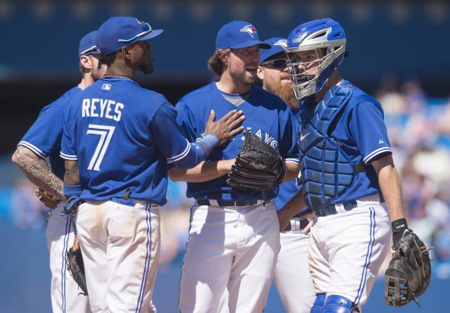 Toronto Blue Jays starting pitcher R.A. Dickey, center, is congratulated by teammates before getting pulled in the ninth inning of a baseball game against the Oakland Athletics in Toronto on Saturday, May 24, 2014. Dickey (5-4) allowed one run and five hits in a season-high 8 1-3 innings. Toronto won 5-2. (AP Photo/The Canadian Press, Darren Calabrese)