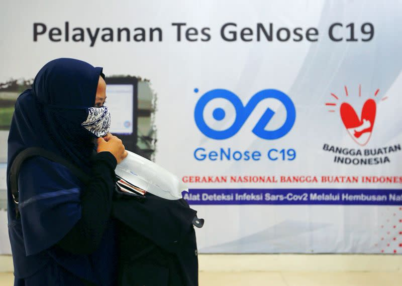 A commuter takes her air-sample to be tested for the COVID-19, in Jakarta