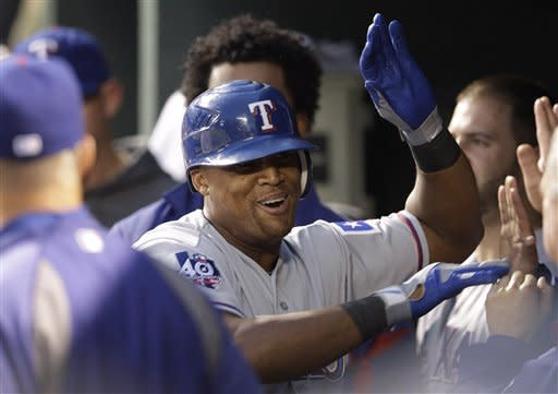 Texas Rangers' Adrian Beltre high-fives teammates in the dugout after hitting a solo home run in the third inning of a baseball game against the Baltimore Orioles in Baltimore, Tuesday, May 8, 2012. (AP Photo/Patrick Semansky)