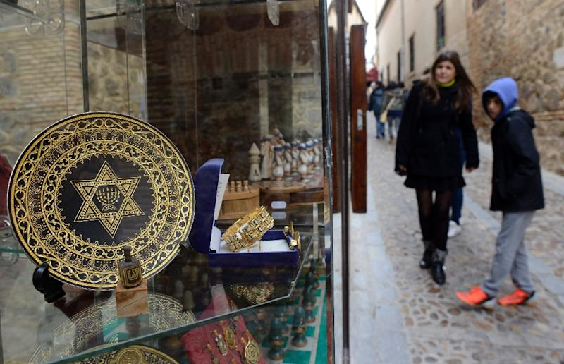 People stand near a gift shop in the old Jewish Quarters of Toledo, Spain, on February 27, 2014 (AFP Photo/Gerard Julien)