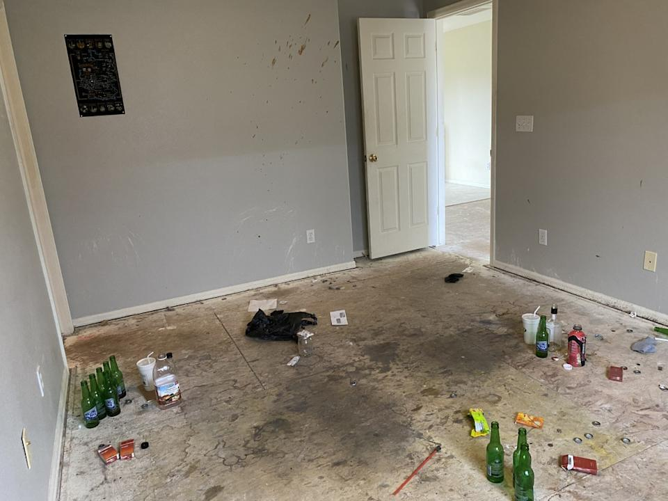 Pictured is the damaged home, with beer bottles and a sleeping mat on the floor. Source: News 5