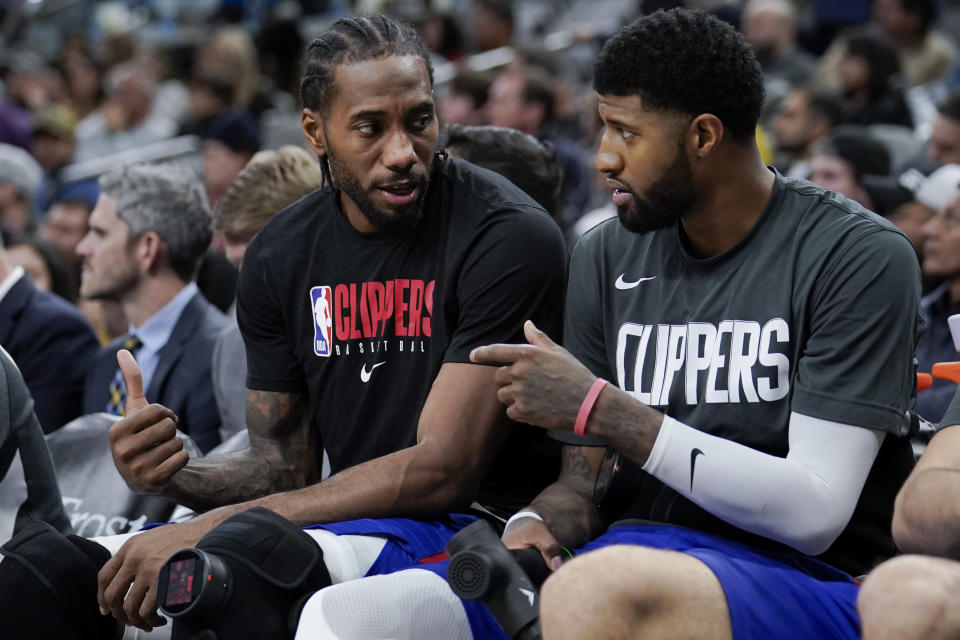 Los Angeles Clippers' Kawhi Leonard, left, and Paul George talk on the bench during the second half of an NBA basketball game against the San Antonio Spurs, Saturday, Dec. 21, 2019, in San Antonio. Los Angeles won 134-109. (AP Photo/Darren Abate)