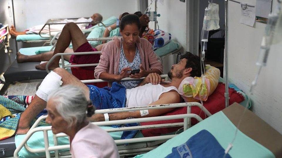 Veronica Calmenarez stands with her husband Luis Alfredo Lopez Molina, (C) both of whom are originally from Venezuela, as he receives health care in the emergency room of the University Hospital Erasmo Meoz after seeking medical care for a severe infection on his leg on March 1, 2019 in Cucuta, Colombia.