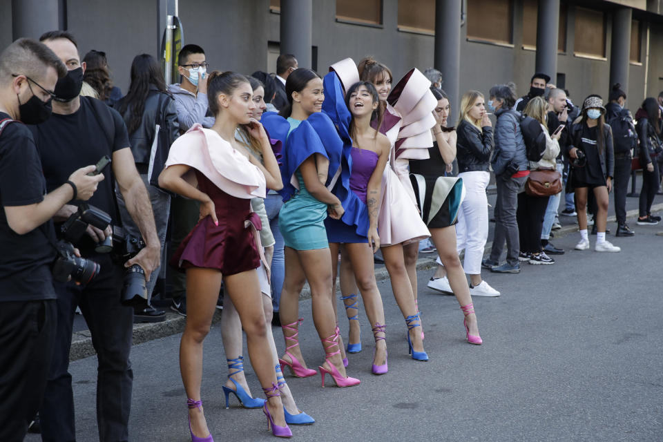 Young models wear creations by fashion student Nora Bourelly on a street outside Valentino women's Spring-Summer 2021 fashion show location, in Milan, Italy, Sunday, Sept. 27, 2020. (AP Photo/Luca Bruno).