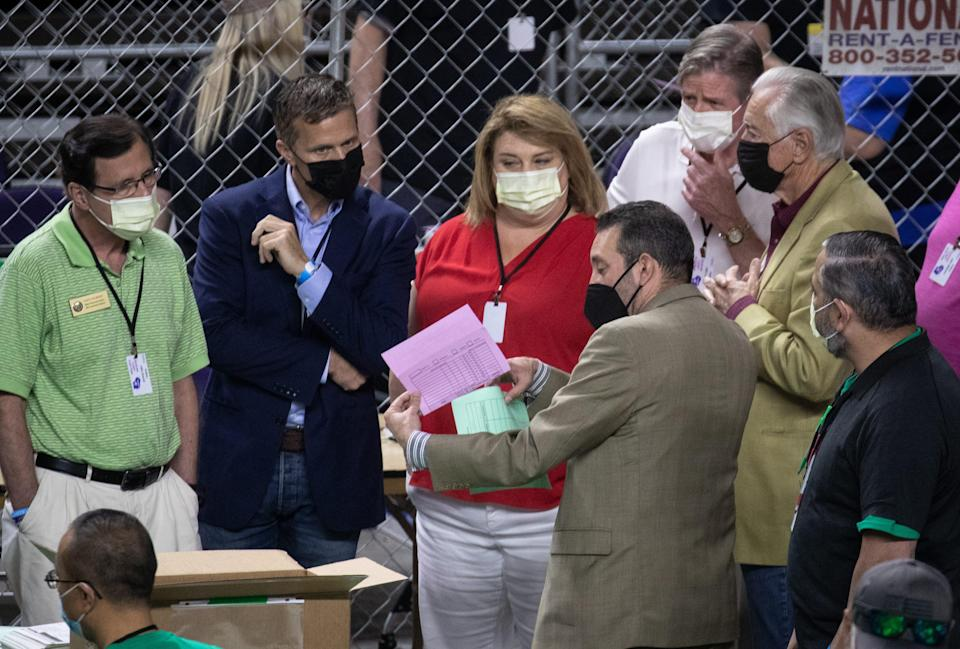 Wisconsin state Rep. Janel Brandtjen, center, former Missouri Gov. Eric Greitens, second from left, and Wisconsin state Rep. Dave Murphy, left, watch as Maricopa County ballots from the 2020 presidential election are examined and recounted by contractors hired by the Arizona Senate on June 12, 2021, at Veterans Memorial Coliseum in Phoenix.